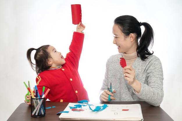 Jonge moeder en dochter spelen papier gesneden