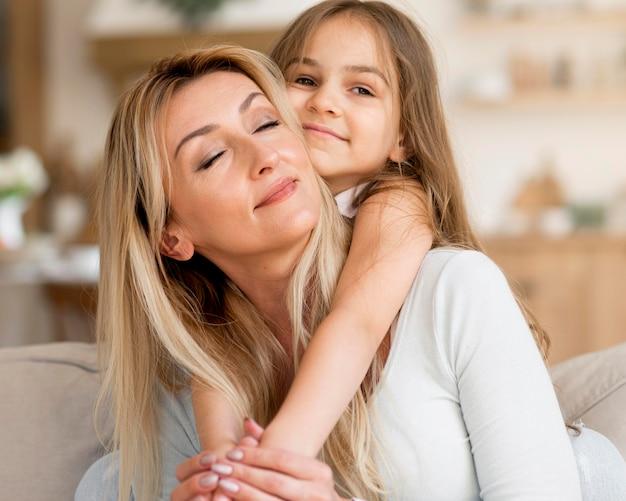 Jonge moeder en dochter thuis omarmd
