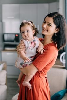 Jonge moeder en dochtertje samen in de keuken thuis