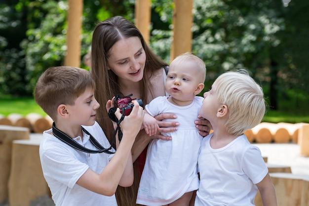 Jonge moeder en drie kinderen in het park. de oudste zoon maakt foto's van broers en zussen. grote gelukkige familie.