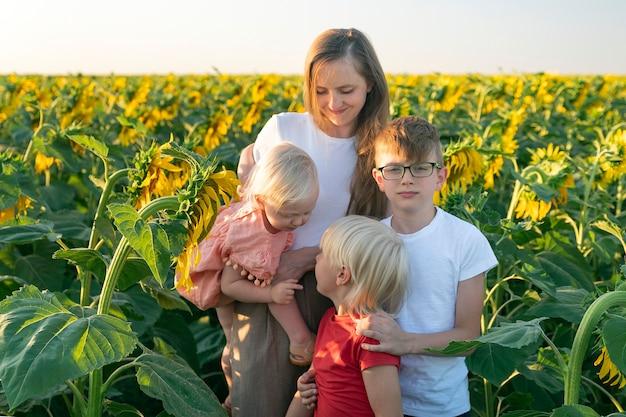 Jonge moeder en drie kinderen op het zonnebloemgebied