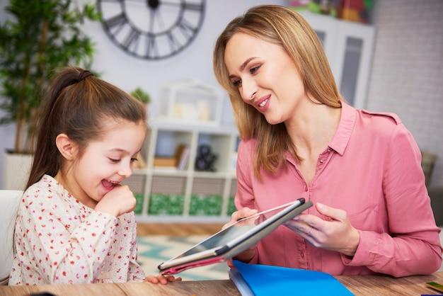 Jonge moeder en haar dochter die thuis een tablet gebruiken