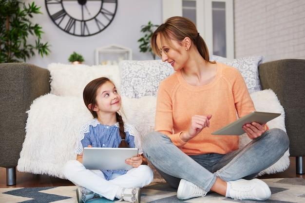 Jonge moeder en haar dochter gebruiken een tablet in de woonkamer living