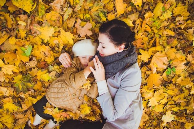 Jonge moeder en haar dochter hebben plezier in de herfst