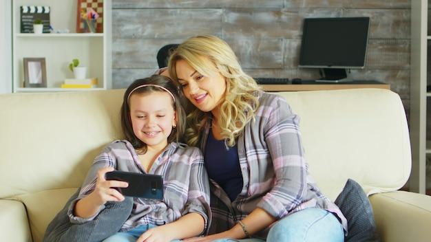 Jonge moeder en haar dochter ontspannen op de bank en kijken naar een grappige video op smartphone.