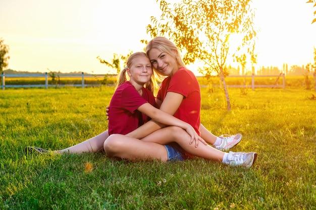 Jonge moeder en haar dochter zitten en knuffelen op de weide bij zonsondergang