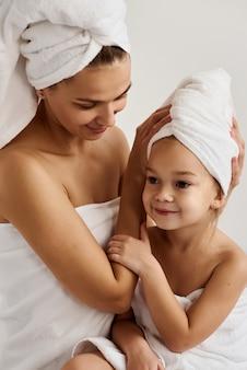 Jonge moeder en haar dochtertje in witte handdoeken in de slaapkamer in de ochtend. gelukkige familie thuis.