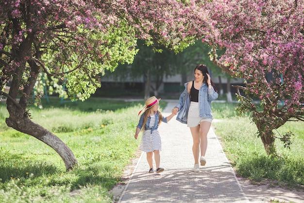 Jonge moeder en haar dochtertje plezier in het voorjaar. mooie moeder en schattig meisje buiten lopen. gelukkige familie samen