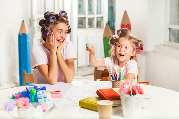 Jonge moeder en haar dochtertje tekenen met potloden thuis