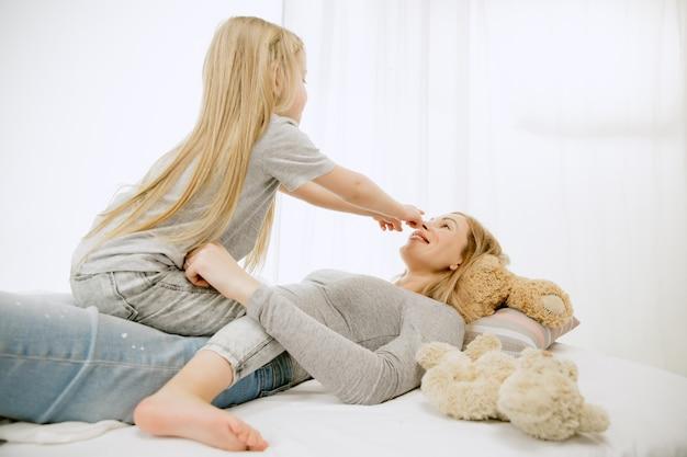 Jonge moeder en haar dochtertje thuis op zonnige ochtend. zachte pastelkleuren. gelukkige familietijd in het weekend. moederdag concept. concepten voor familie, liefde, levensstijl, moederschap en tedere momenten.
