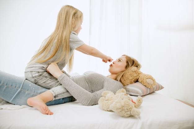 Jonge moeder en haar dochtertje thuis op zonnige ochtend. zachte pastelkleuren. gelukkige familietijd in het weekend. moederdag concept