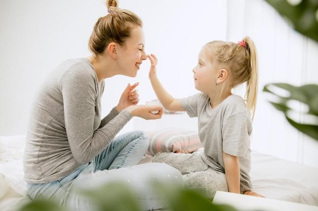 Jonge moeder en haar dochtertje thuis op zonnige ochtend. zachte pastelkleuren. gelukkige familietijd in het weekend.