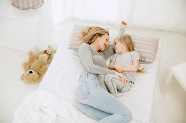 Jonge moeder en haar dochtertje thuis op zonnige ochtend.