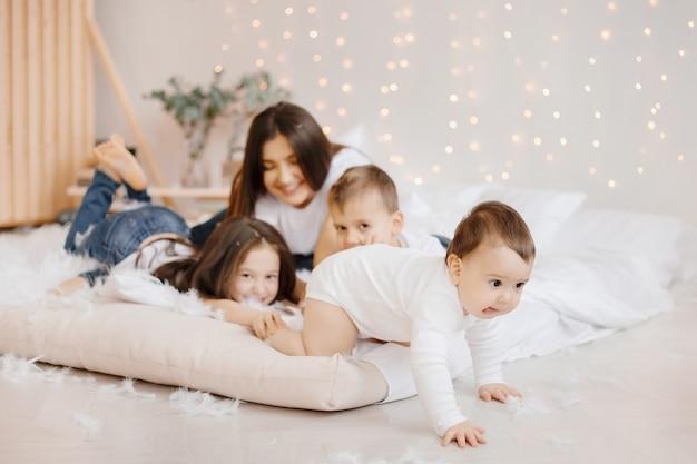Jonge moeder en haar drie kinderen in jeans en t-shirts spelen met plezier zittend op de vloer
