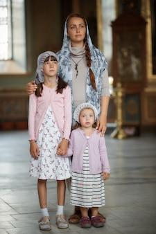Jonge moeder en haar kleine blonde blanke dochter met kaarsen in orthodoxe russische kerk