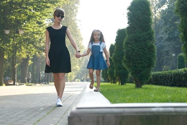 Jonge moeder en haar kleine dochter met lang haar lopen samen hand in hand in het zomerpark.