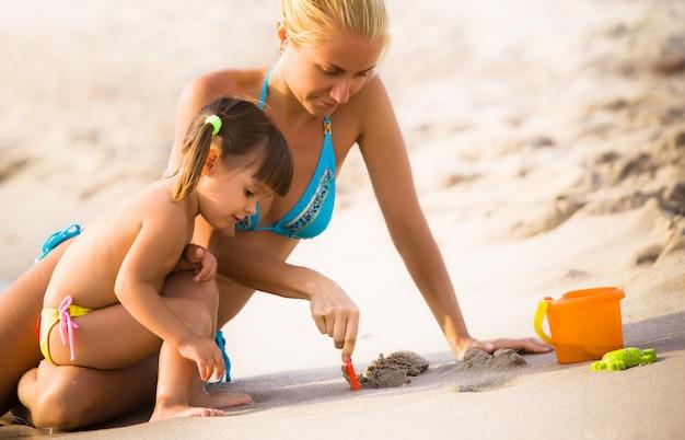 Jonge moeder en haar kleine dochter zittend op zandstrand en spelen