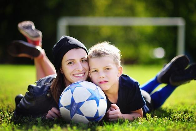 Jonge moeder en haar kleine jongen die een voetbalspel op zonnige de zomerdag speelt. familie plezier met de bal buitenshuis