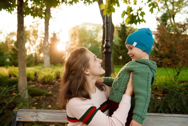 Jonge moeder en haar peuterjongen hebben plezier in de herfst