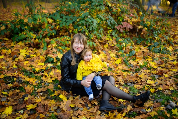 Jonge moeder en haar peutermeisje in de herfstgebieden