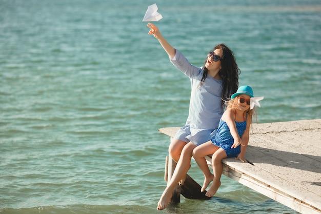 Jonge moeder en haar schattige dochter aan de zeezijde lanceren papieren vliegtuigen in de lucht en lachen