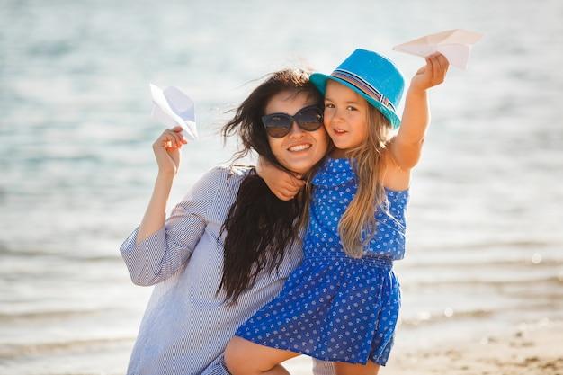 Jonge moeder en haar schattige dochter aan de zeezijde lanceren papieren vliegtuigjes in de lucht en lachen