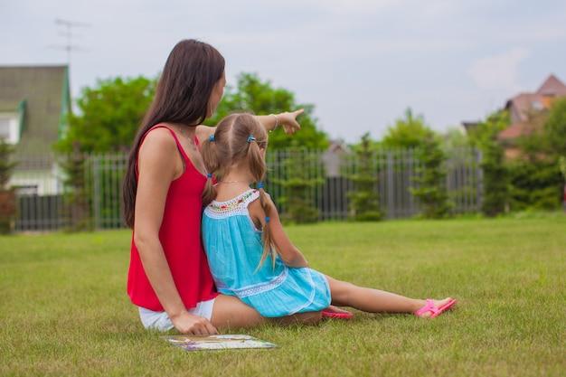 Jonge moeder en haar schattige dochter genieten van de vakantie op gras in de buurt van huis