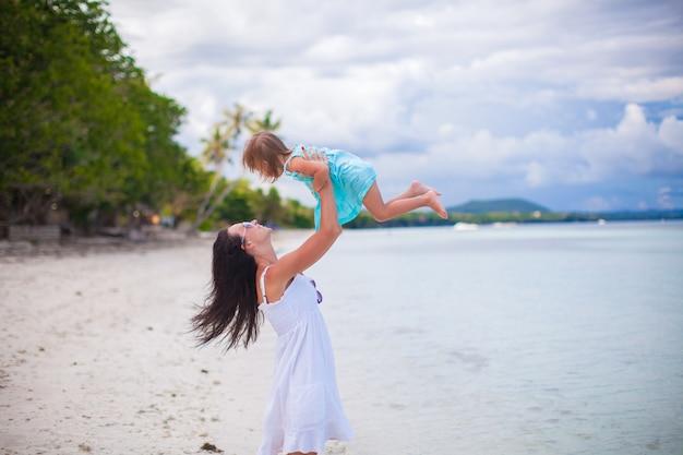 Jonge moeder en haar schattige dochter hebben plezier op exotisch strand