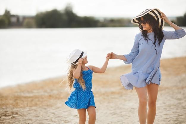 Jonge moeder en haar schattige dochter op het strand plezier. mooie familie vakantie. klein vrolijk kind met haar moeder aan de zee.