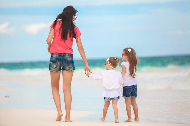 Jonge moeder en haar schattige dochters lopen op tropisch strand