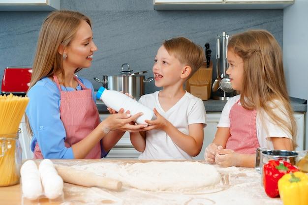 Jonge moeder en haar schattige kinderen pizza samen koken in de keuken
