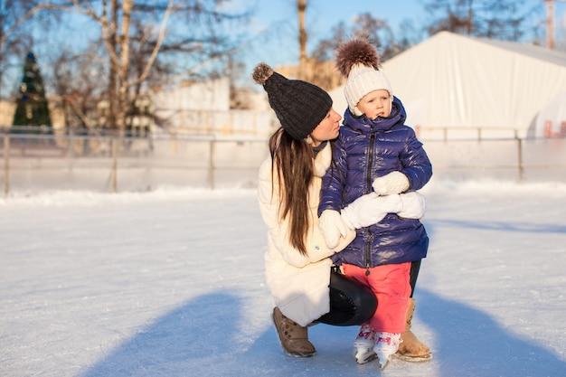 Jonge moeder en haar schattige kleine dochter op een ijsbaan