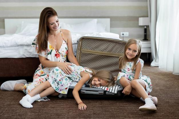 Jonge moeder en haar tweelingdochters met een koffer in een hotelkamer.