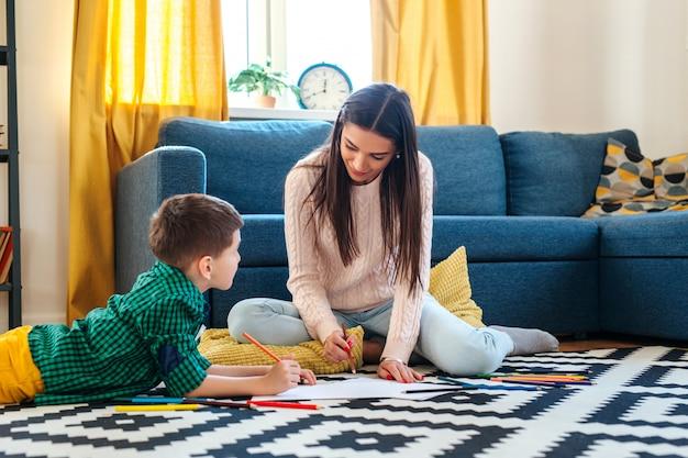 Jonge moeder en haar zoontje samentrekken thuis. gemengd ras familie