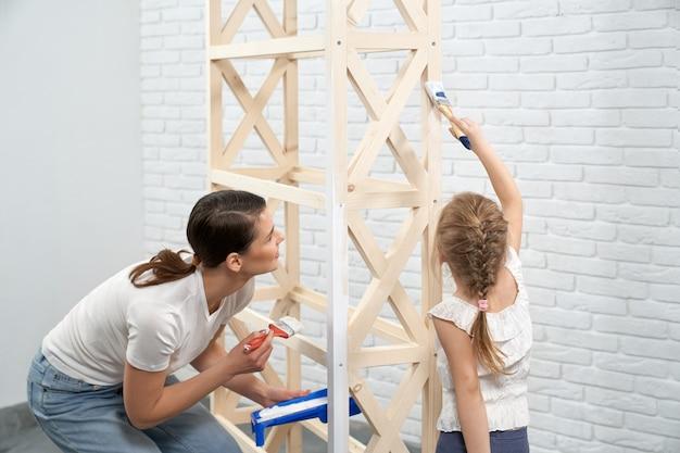 Jonge moeder en kind die houten rek schilderen