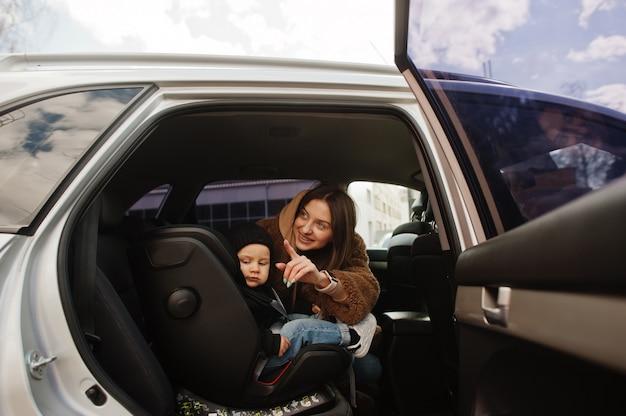 Jonge moeder en kind in de auto. kinderzitje op stoel. rijden veiligheidsconcept.