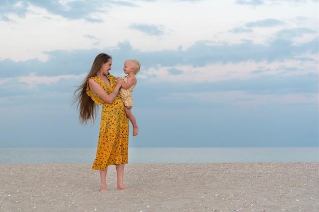 Jonge moeder en kind op een zandstrand op zee en hemel achtergrond.