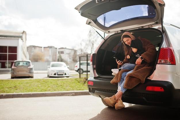 Jonge moeder en kind zitten in de kofferbak van een auto en kijken naar mobiele telefoon. rijden veiligheidsconcept.