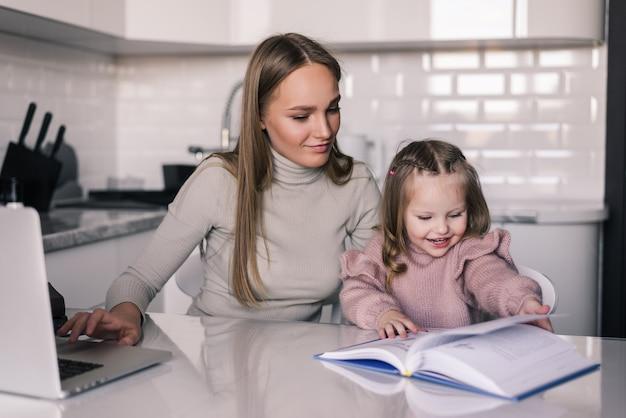 Jonge moeder en kinddochter die thuiswerk doen en thuis schrijven die lezen