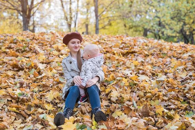 Jonge moeder en klein kind zittend op gele herfstbladeren in park