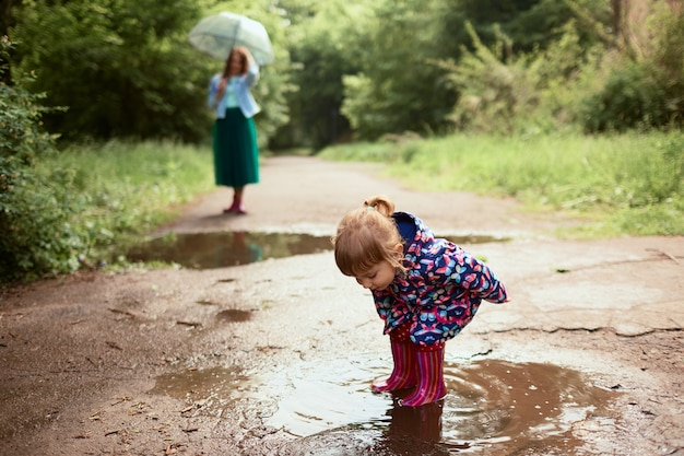 Jonge moeder en kleine dochter hebben plezier wandelen in rubberlaarzen op de zwembaden in het park