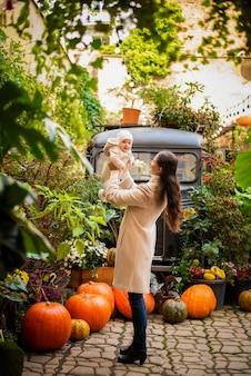 Jonge moeder en kleine dochter op pompoenenachtergrond, halloween-vooravond