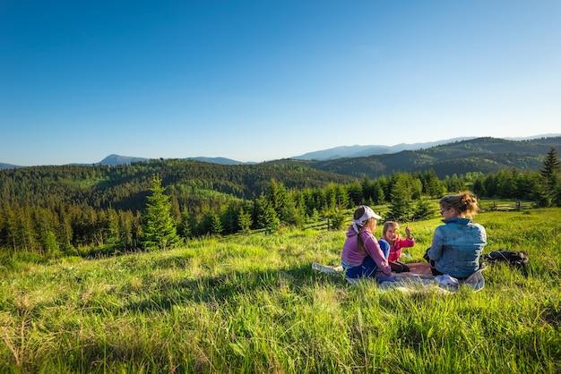 Jonge moeder en kleine dochters liggen op een met gras overwoekerde helling of bewonderen het prachtige uitzicht van een vos die op de heuvels groeit