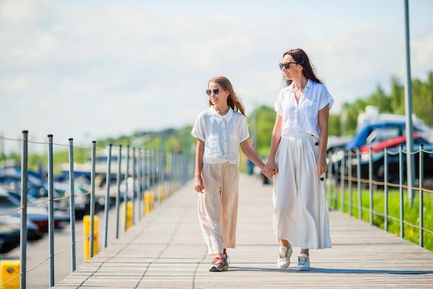Jonge moeder en meisje in de haven in de zomer