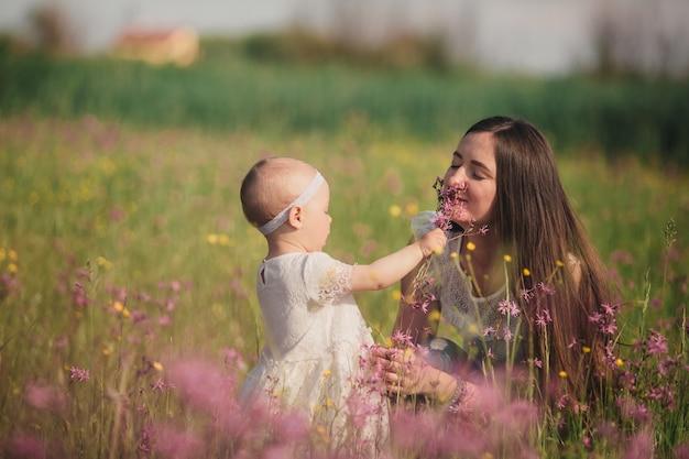 Jonge moeder en schattig dochtertje lopen en spelen in veld met wilde bloemen.