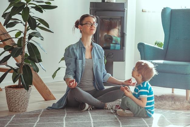 Jonge moeder en schattig kind doen samen yoga thuis zittend op de vloer
