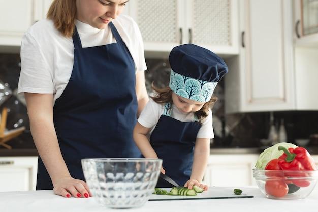 Jonge moeder en schattig schattig meisje kind dragen schort hakkende groenten