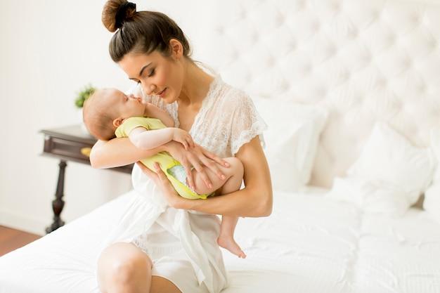 Jonge moeder en schattige baby meisje op het bed