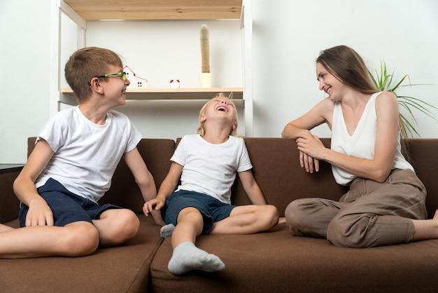 Jonge moeder en twee kinderen zitten op de bank en hebben plezier met praten. familievriendelijke relaties.