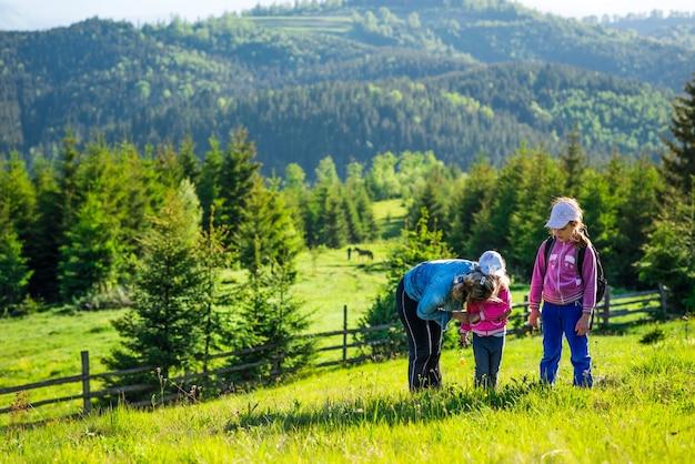 Jonge moeder en twee kleine dochters reizigers staan op een helling met een prachtig uitzicht op de heuvels bedekt met dicht sparrenbos tegen de blauwe lucht